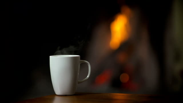 Cup of hot beverage in front of a burning fireplace