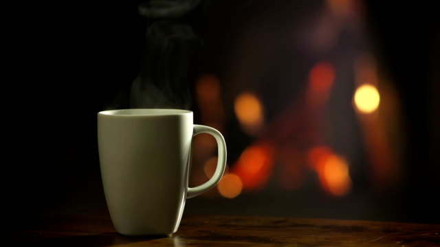 cup of hot beverage in front of a fireplace - steam stock videos & royalty-free footage