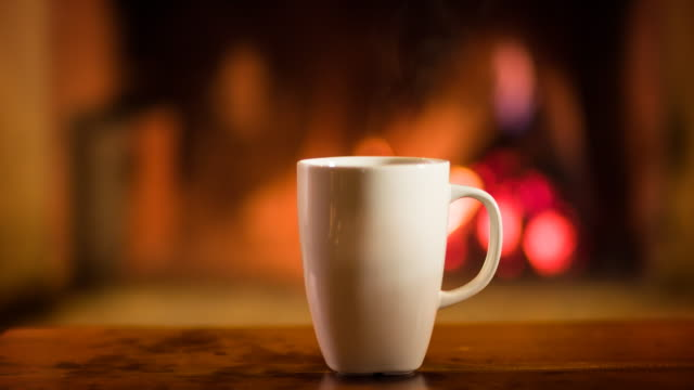Cup of hot beverage in front of a fireplace