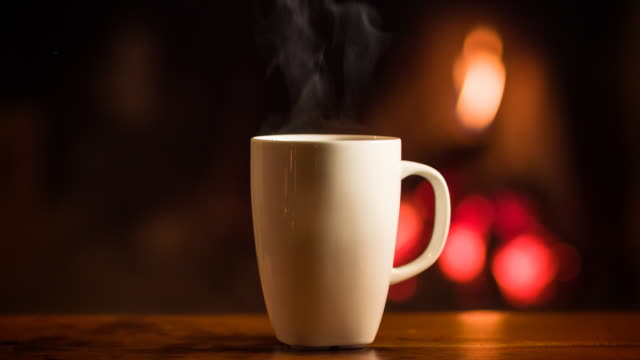 cup of hot beverage in front of a fireplace - chalet stock videos & royalty-free footage