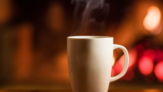 cup of hot beverage in front of a fireplace - hot chocolate stock videos and b-roll footage