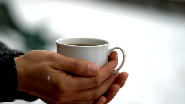Tasse heißen Kaffee unter Schnee