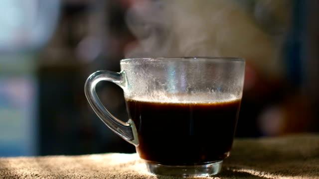 Eine Tasse heißen Kaffee mit Bach und schönen Sonnenlicht