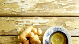 Cup of lemon tea with ginger on wooden floor 4K 4k