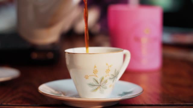 vídeos de stock, filmes e b-roll de cup of tea poured from teapot - cultura inglesa