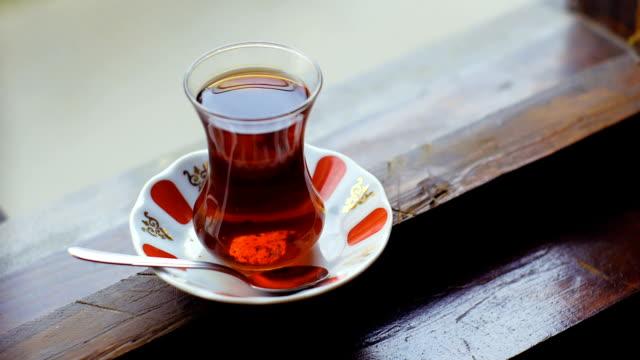 vidéos et rushes de tasse de thé turc sur une fenêtre - thé noir
