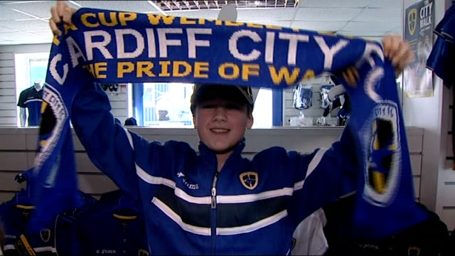 preview cardiff city logo on stadium gate lewis rowlands set up holding scarf and interview sot shoppers having their photographs taken standing with... - neckwear stock videos and b-roll footage
