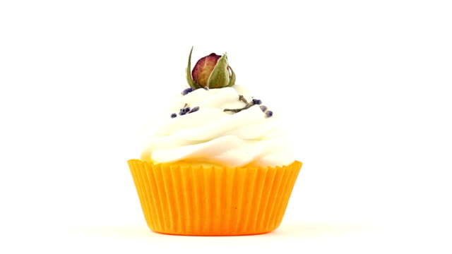 Cupcake with rose in front of white background