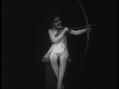 vídeos de stock, filmes e b-roll de b/w 1916 cupid sitting on column shoots arrow to side + cheers - flecha