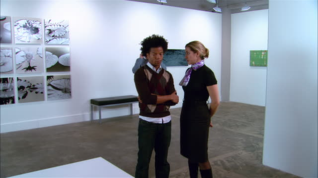 curator and artist planning exhibition in gallery as gallery owner talks on cell phone in background / owner getting off phone and coming over to join discussion / everyone shaking hands at end of conversation - curator stock videos & royalty-free footage