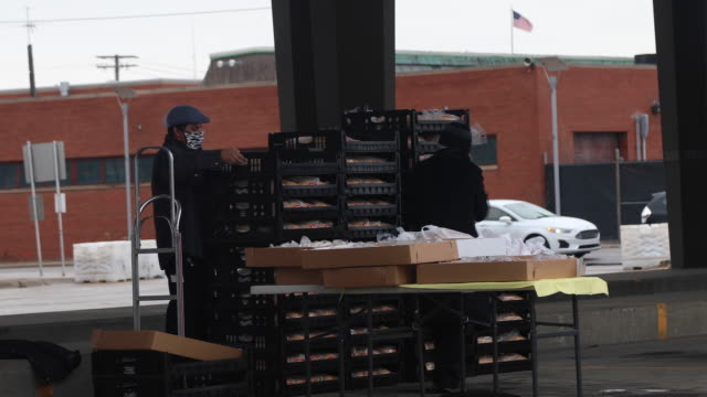 curbside grocery shopping pick-up at eastern market in detroit and a michigan health professionals covid-19 drive through testing site in detroit,... - クリーンスーツ点の映像素材/bロール