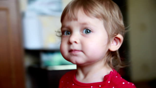 curious baby peeking at the camera and hands out a small shoe - little girls giving head stock videos and b-roll footage