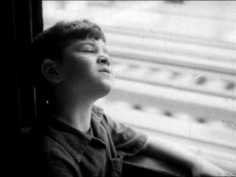 vídeos de stock e filmes b-roll de b/w 1945 curious boy looking out of window of elevated train / nyc / educational - comboio elevado