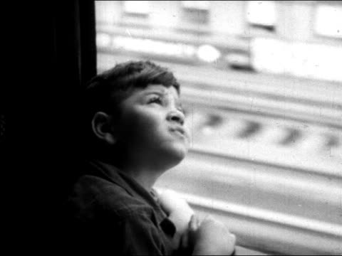 stockvideo's en b-roll-footage met b/w 1945 curious boy looking up out of window of elevated train / nyc / educational - alleen jongens