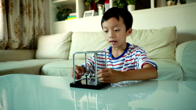curious boy playing with newtons cradle - perpetual motion stock videos & royalty-free footage