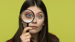 Curious brunette woman looking into camera through magnifying glass, spying, inspecting
