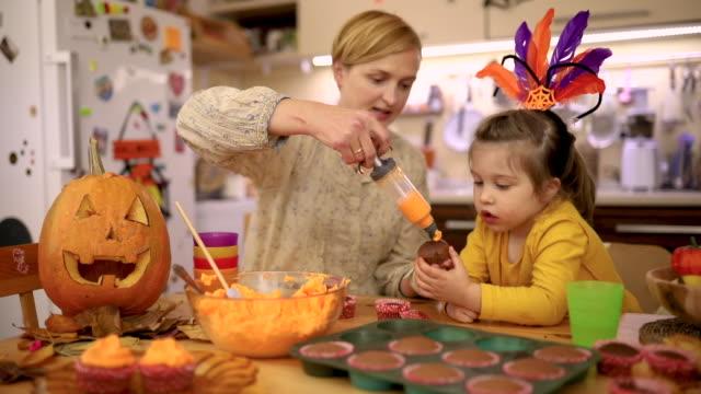 vídeos y material grabado en eventos de stock de hija curiosa observando a su madre mientras ella decora un cupcake de halloween con glaseado de naranja de la cuerda - decoration