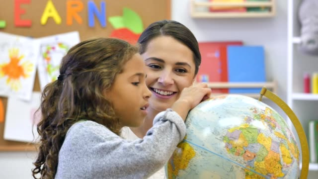 curious elementary schoolgirl studies globe - geografia fisica video stock e b–roll