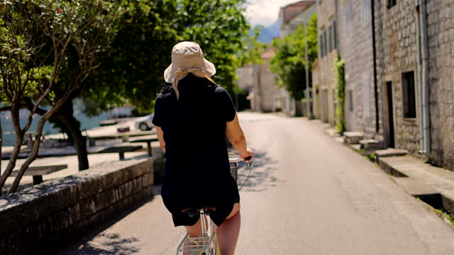 stockvideo's en b-roll-footage met curious female tourist exploring the majestic old town near pier with her bike - hoofddeksel