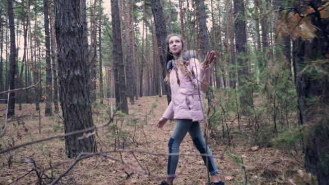 Neugierige Mädchen in rosa Mantel umzusehen bei einem Spaziergang im Wald