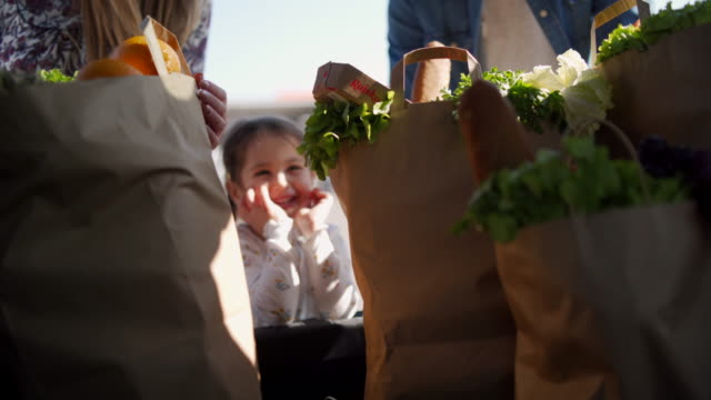curious little girl helping parent around groceries - paper bag stock videos & royalty-free footage