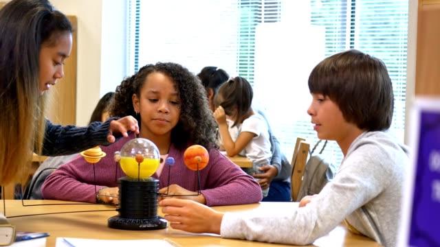vídeos de stock e filmes b-roll de curious middle school students learn about the solar sytem - aluna da escola secundária