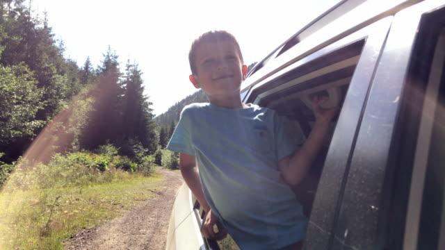 neugieriger kleiner junge schaut aus fenster während der fahrt im auto - video stock-videos und b-roll-filmmaterial