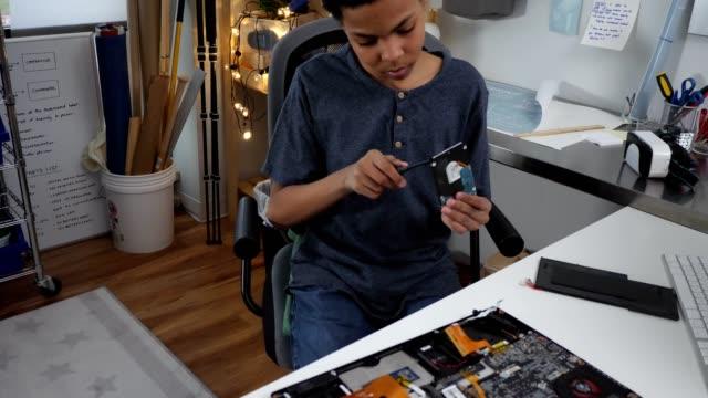 Nieuwsgierige tiener jongen demonteren laptop harde schijf
