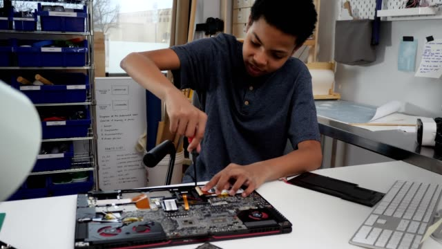 curious teenage boy repairs laptop in home workshop - repairing stock videos & royalty-free footage