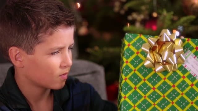 curious young boy shakes present intently in front of christmas tree - christmas present stock videos & royalty-free footage