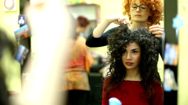 curly brunette girl getting her new hair style at hairstylist - beauty salon stock videos and b-roll footage