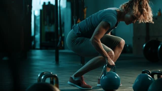巻き毛の女性ジムでケトルベルで運動を行う - しゃがむ点の映像素材/bロール