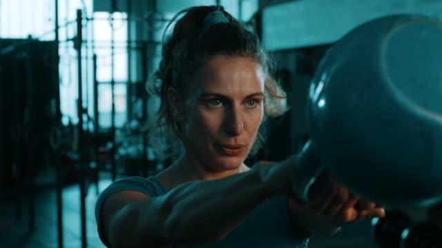 vidéos et rushes de femmes cheveux bouclés, faire des exercices avec kettlebell en gym - entraînement croisé