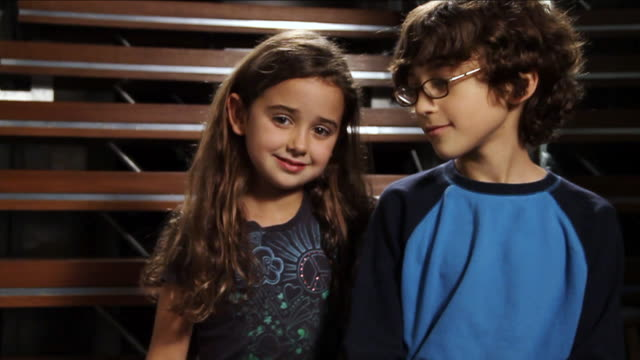 vidéos et rushes de ms curly haired girl and kid with glasses hugging each other and smiling / miami, florida, united states  - petits garçons