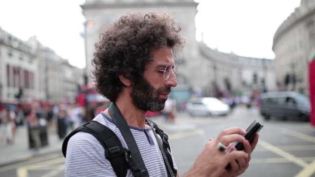 lockly haired male traveler searching an address with his mobile phone - adressbuch stock-videos und b-roll-filmmaterial