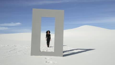 stockvideo's en b-roll-footage met curly haired woman walks through doorframe in desert, wide - solitair