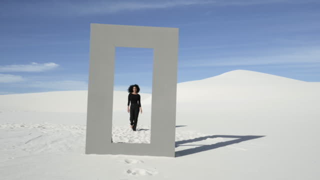 vídeos y material grabado en eventos de stock de curly haired woman walks through doorframe in desert, wide - chance