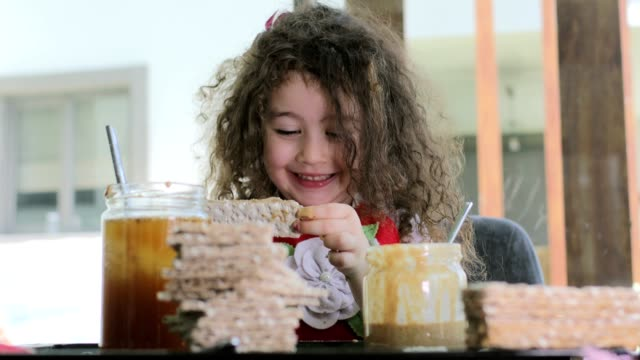 curly haired young mother and curly haired daughter are making homemade wafers at home. they use honey chocolate and peanut butter. the little girl learns to cook from her mother. they're having fun together during covid-19 quarantine days. - dieting stock videos & royalty-free footage