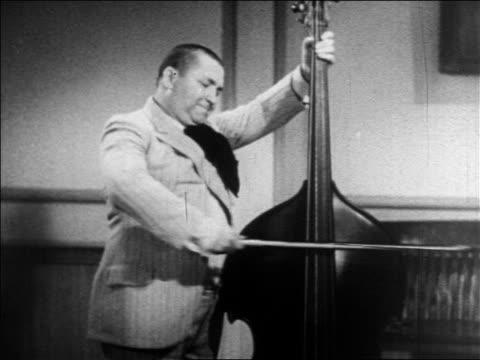 vídeos y material grabado en eventos de stock de curly of the 3 stooges playing double bass with bow / feature - sólo hombres jóvenes