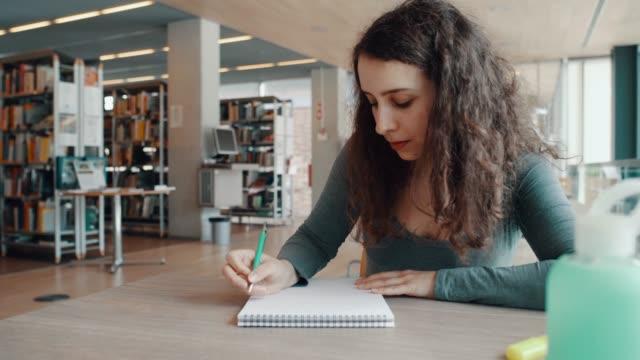 vídeos de stock, filmes e b-roll de ensaio de escrita mulher encaracolado na biblioteca - estudante universitária