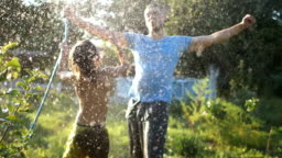 Curly-haired boy squirting his father with a hose. Holidays in the village, father's day
