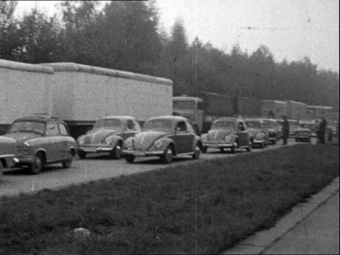 Currency devalued EAST GERMANY Helmstedt EXT PAN traffic stopped on border road / Ditto police speaks to driver / BV Cars PAN to notice 'Allied...