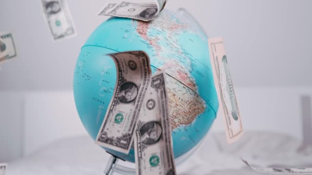 US currency dollar bills falling over globe, slow motion