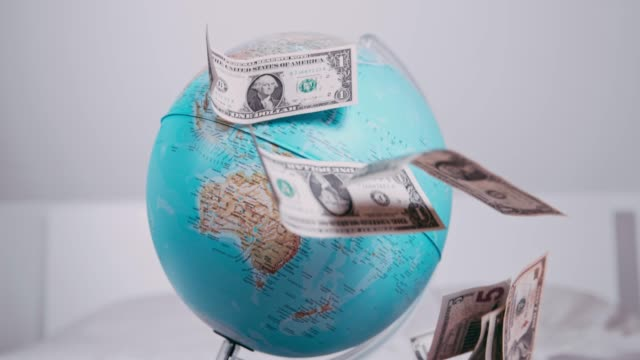 US currency dollar bills falling over spinning globe, slow motion