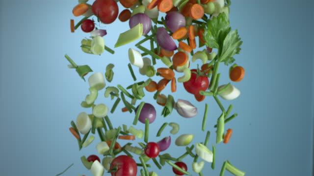 vídeos de stock, filmes e b-roll de curtain of vegetables falling - fundo azul