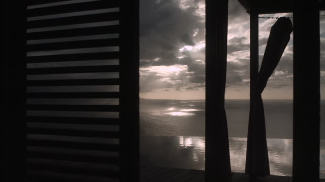 curtains and slats in front of infinity pool and ocean - infinity pool stock videos & royalty-free footage