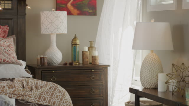 curtains billow in the breeze from an open window in the interior of a master bedroom featuring bed, end tables, lamps and decorator items. - pillow stock videos and b-roll footage