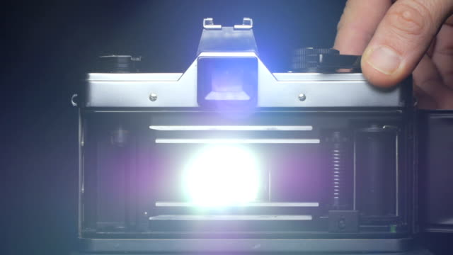 curtains of slr film camera opens and lets the light hit the film while hand pushes the shutter button - slr camera stock videos and b-roll footage