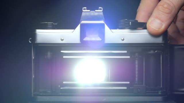Vorhänge von slr Filmkamera öffnet und lässt das Licht den Film getroffen, während Hand den Auslöser drückt