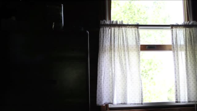 Curtains rustle in a cottage window.